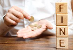 Blocos de madeira com a multa da palavra e um homem que calcule o tamanho da multa Pena monetária imposta sob a forma da punição imagem de stock royalty free