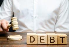 Blocos de madeira com o débito da palavra e juiz com um martelo O conceito da punição judicial para o não-pagamento do débito pro imagem de stock royalty free