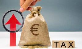 Blocos de madeira com o imposto da palavra, acima da seta e do saco do dinheiro O conceito do crescimento do imposto no país Impo imagens de stock