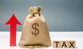 Blocos de madeira com o imposto da palavra, acima da seta e do saco do dinheiro O conceito do crescimento do imposto no país Impo fotografia de stock royalty free