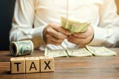 Blocos de madeira com o imposto da palavra e um homem de negócios que conte o dinheiro O conceito do pagamento do tempo dos impos imagens de stock royalty free