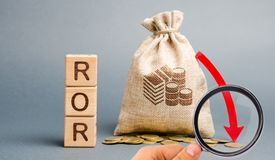 Blocos de madeira com a palavra ROR, o saco do dinheiro e para baixo a seta Rela??o financeira que ilustra o n?vel de perda de ne foto de stock