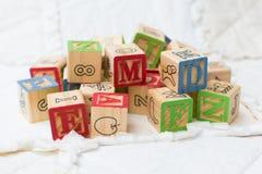 Blocos de madeira do alfabeto na edredão em uma pilha Fotografia de Stock Royalty Free
