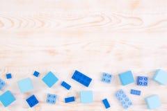 Blocos de madeira e plásticos azuis no fundo de madeira, vista superior com espaço da cópia foto de stock