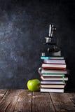 Blocos de notas, microscópio e maçã na frente da placa de giz imagens de stock royalty free