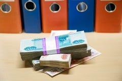 Blocos do dinheiro no fundo de dobradores coloridos do negócio Foto de Stock Royalty Free