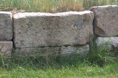 blocos drystone Áspero-desbastados usados em uma parede de retenção com o musgo que cresce nas quebras entre elas imagem de stock
