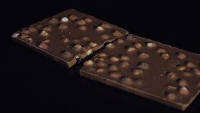 Blocos escuros do chocolate com filtração lenta do close-up dos detalhes das porcas Perspectiva feita de barras de chocolate video estoque