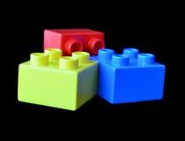 Blocos multicoloured plásticos do construtor no fundo preto Fotografia de Stock