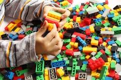 Blocos plásticos do brinquedo da construção da mão do ` s da criança com fundo borrado Imagens de Stock