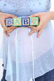 Blocos que soletram o bebê acima de esperar a barriga da mamã fotos de stock royalty free