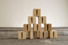Blocs avec des silhouettes d'homme d'affaires structurés dans une pyramide Photo libre de droits
