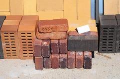 Blocs constitutifs colorés, briques et machines à paver concrètes (pavé) ou blocs de patio organisés sur des palettes à vendre Images stock