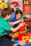 Blocs constitutifs d'enfants dans le jardin d'enfants Enfants de groupe jouant le plancher de jouet Photo stock