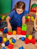 Blocs constitutifs d'enfants dans le jardin d'enfants Enfants de groupe jouant le plancher de jouet Image libre de droits