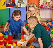 Blocs constitutifs d'enfants dans le jardin d'enfants Enfants de groupe jouant le plancher de jouet Photos stock