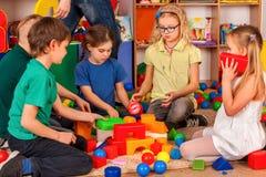 Blocs constitutifs d'enfants dans le jardin d'enfants Enfants de groupe jouant le plancher de jouet photographie stock libre de droits