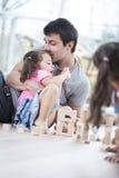 Blocs constitutifs de baiser de fille de père affectueux sur le plancher Photos libres de droits