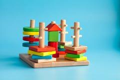 Blocs constitutifs de jouet en bois coloré avec des jouets sur un fond bleu Photo libre de droits