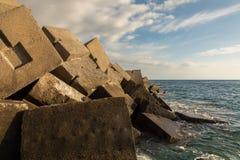 Blocs de brise-lames dans le port du Porto Rico, mamie Canaria, avec l'Océan Atlantique à l'arrière-plan Images libres de droits