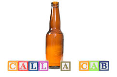 Blocs de lettre orthographiant l'appel une cabine avec une bouteille à bière Photographie stock libre de droits
