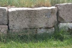 Blocs de pierres sèches taillés grossièrement utilisés dans un mur de soutènement avec de la mousse s'élevant dans les fissures e Image stock
