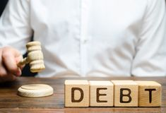 Blocs en bois avec la dette de mot et juge avec un marteau Le concept de la punition juridique pour le non-paiement de la dette p image libre de droits