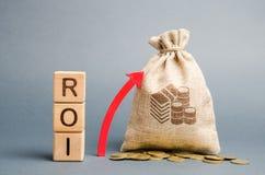Blocs en bois avec le mot ROI et la fl?che haute avec le sac d'argent Haut niveau de la rentabilit? d'affaires Retour sur l'inves image libre de droits