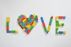 Blocs en bois colorés de jouet comme coeur dans l'AMOUR Image libre de droits