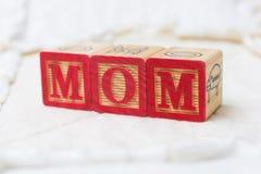 Blocs en bois d'alphabet sur la maman d'orthographe d'édredon Photo libre de droits