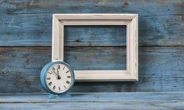 Blocs en bois de cadre vide avec le réveil de vintage Image stock