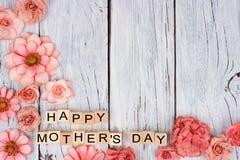 Blocs en bois heureux de jour de mères avec la frontière de coin de fleur sur le bois blanc Photographie stock libre de droits