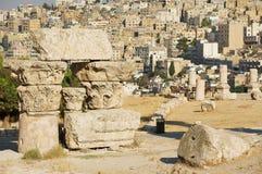 Blocs en pierre antiques des colonnes ruinées à la citadelle d'Amman avec la ville au fond à Amman, Jordanie Photographie stock libre de droits
