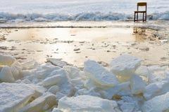 Blocs et chaise de glace sur le bord du glace-trou Image libre de droits