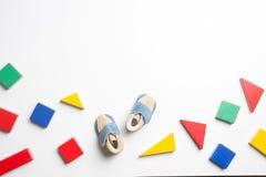 Blocs et chaussures de bébé en bois colorés sur le fond blanc Image stock