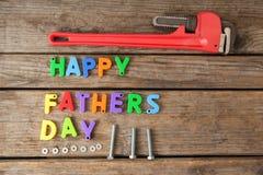 Blocs et outils manuels heureux de jour de pères sur la planche en bois Photo stock