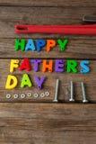 Blocs et outils manuels heureux de jour de pères sur la planche en bois Photographie stock