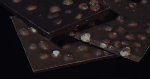Blocs foncés de chocolat avec cuisson en gros plan lente de détails d'écrous la macro Perspective faite de barres de chocolat banque de vidéos