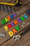 Blocs heureux de jour de pères, bande de mesure, lien et outils manuels sur la planche en bois Image stock