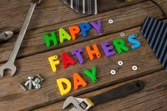 Blocs, lien et outils manuels heureux de jour de pères sur la planche en bois Photo libre de droits