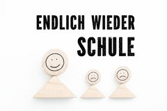 """Blocs symbolisant le parent avec des enfants et la phrase """"de nouveau à l'école, finalement """"en allemand photographie stock"""