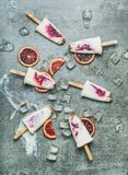 Blodapelsin-, yoghurt- och granolaisglassar på is, konkret bakgrund arkivbilder