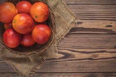 Blodapelsinfrukt i en vide- korg på den mörka trätabellen Royaltyfri Foto