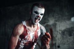 Blodig clown-galning med yxa Arkivbild