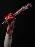 Blodig hand som rymmer en justerbar skiftnyckel, blodig tangent, galen rörmokare, blodigt tema, halloween tema, svart bakgrund so Fotografering för Bildbyråer