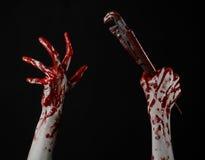 Blodig hand som rymmer en justerbar skiftnyckel, blodig tangent, galen rörmokare, blodigt tema, halloween tema, svart bakgrund so Arkivfoton