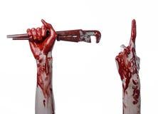 Blodig hand som rymmer en justerbar skiftnyckel, blodig tangent, galen rörmokare, blodigt tema, halloween tema, vit bakgrund som  Arkivbilder