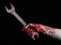 Blodig hand som rymmer en stor skiftnyckel, blodig skiftnyckel, stor tangent, blodigt tema, halloween tema, galen mekaniker, svar Royaltyfri Fotografi