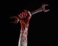 Blodig hand som rymmer en stor skiftnyckel, blodig skiftnyckel, stor tangent, blodigt tema, halloween tema, galen mekaniker, svar Fotografering för Bildbyråer