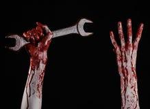 Blodig hand som rymmer en stor skiftnyckel, blodig skiftnyckel, stor tangent, blodigt tema, halloween tema, galen mekaniker, svar Royaltyfri Foto
